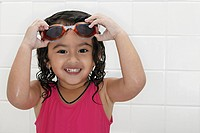 Little girl in bath tub with swimsuit and goggles.