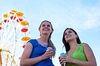 Teenagers eating snow cones by the ferris wheel at