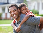 Smiling African American father piggybacking son