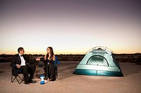 Couple in formal attire toasting champagne glasses outside tent in desert