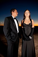 Serious couple in formal attire standing in desert