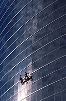 Two men cleaning windows on high rise building