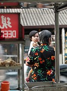 Young Chinese girl and grandmother standing outside hawker stall in Penang, Malaysia
