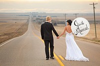 three hills, alberta, canada, a bride and groom on a rural road with the bride holding a parasol with the words ´just married´ written on it