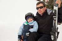 red deer, alberta, canada, a man with a young boy holding skis at a ski hill