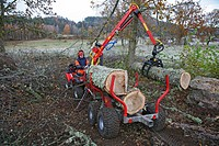 Tree surgeon. Arborist using a small crane, grapple and trailer to remove sections of pruned and felled trees from a woodland area. Photographed in Bo...