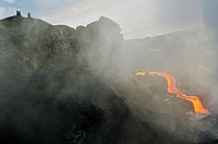 People watching river of molten lava flowing to the sea, Kilauea Volcano, Hawaii Islands, USA.