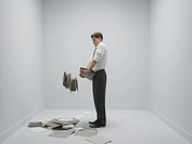 Office stress. Conceptual image of work related stress represented by a businessman dropping an overload of paperwork in an office.