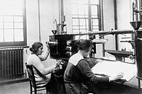 Testing thermometers. Laboratory technicians analysing thermometers using testing equipment. The thermometers are lowered into an electrically heated ...