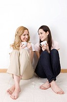 Tow women sitting together drinking coffee