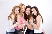 Four young women standing together, thumbs up