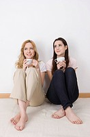 Two young women sitting together with coffee