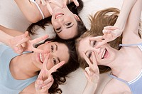 Three young women lying in circle making peace sign