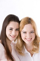 Two young woman smiling head to head