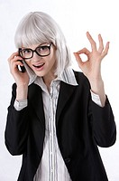 Young businesswoman giving ok sign, talking on the phone