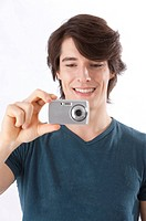 Young man taking pictures with digital camera, smiling