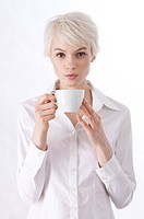 Young woman holding a cup of coffee and blowing