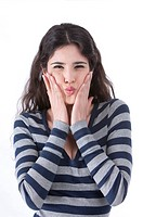 Young woman squeezing face with hands, making funny expression