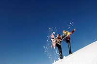 Young couple splashing snow with snow shoes, low angle view