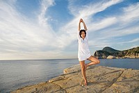 Portrait of a brunette woman doing yoga in a cliff in Ibiza, Balearic Islands