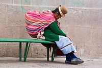 Quechuan woman traditionally dressed is resting on a bench, Cuzco, Peru