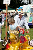 Man in hat operating hand powered fairground ride for toddlers