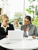 Businesswomen sitting at outside cafe table using laptop