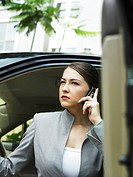 Businesswoman answering a phone call, about to get out of car