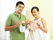 Couple holding baby bibs