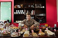 Cafe owner, assorted pastries and baked goods on counter (thumbnail)