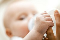 Baby drinking from bottle and holding mother's finger, close_up