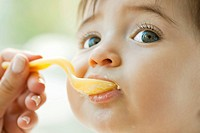 Infant being fed with a spoon