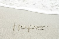 The word hope written in the sand at the beach