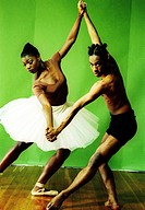Male and female ballet dancers holding hands of each other and dancing
