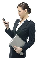 Businesswoman holding a laptop and looking at a mobile phone