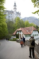 Japanese tourist taking a picture of Neuschwanstein castle, Bavaria, Germany