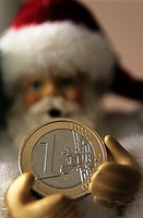 Santa Claus doll holding out a euro coin.