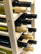 Bottled wine and a wine rack isolated against a white background