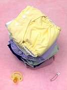 A stack of modern cloth nappies isolated against a pink background