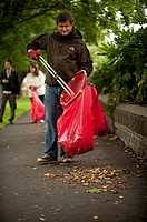 Adult volunteers collecting litter in a park, Aberystwyth Wales UK