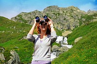Girl with binoculars in mountains