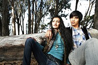 Portrait of young couple sitting outdoors.