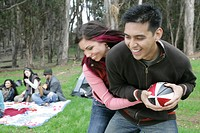 Young playful couple playing football