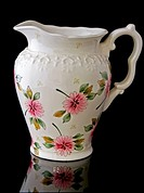 This stock image is a cream colored, floral water pitcher for home decor accent use, isolated on a black background with a beautiful reflected image i...