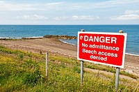 Danger sign on beach near Whitehaven marina and harbour on the west coast of Cumbria , England , Great britain , Uk