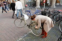 Young woman unlock her bike, streetscene, Utrecht, Netherlands