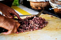 Detail of chef´s hands as he chops meat with knife on a white cutting board in a street cafe, San Felipe, Baja California, Mexico