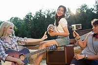Woman with guitar and friends outside