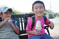 Boys sitting on bench eating ice cream, Japan