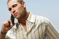 Portrait of young man in striped shirt on cell phone